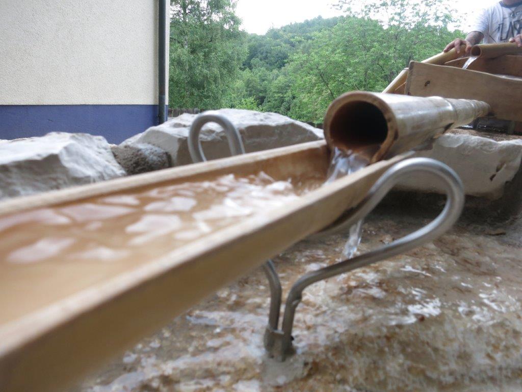 WASSERSPIEL aus Bambusrohren und halbiertem Bambus als Rinne zur Wasserführung